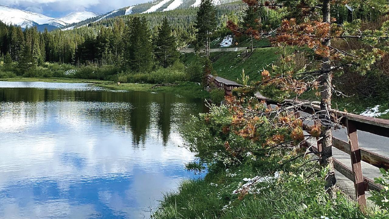 Serene lake vista overlaid with Rendezvous Colorado logo