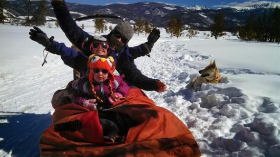 Mom and two children on a winter sled ride.