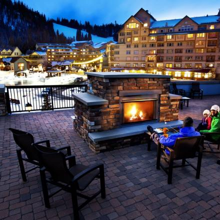 Family sits fireside at Winter Park Resort in Winter Park, Colorado