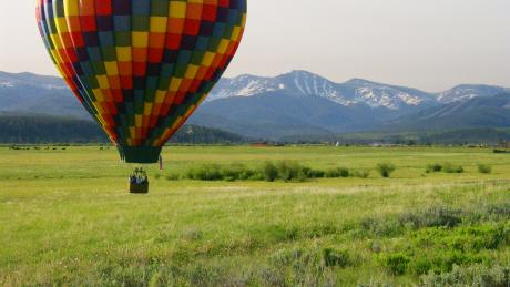Hot Air Balloon soaring over a meadow in Winter park, Colorado