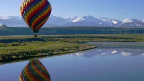 Hot Air Balloon over a lake with frosted peaks in the background in Winter Park, Colorado